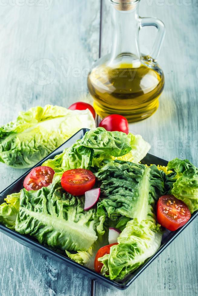 Fresh lettuce salad with cherry tomatoes  radish and carafe. photo