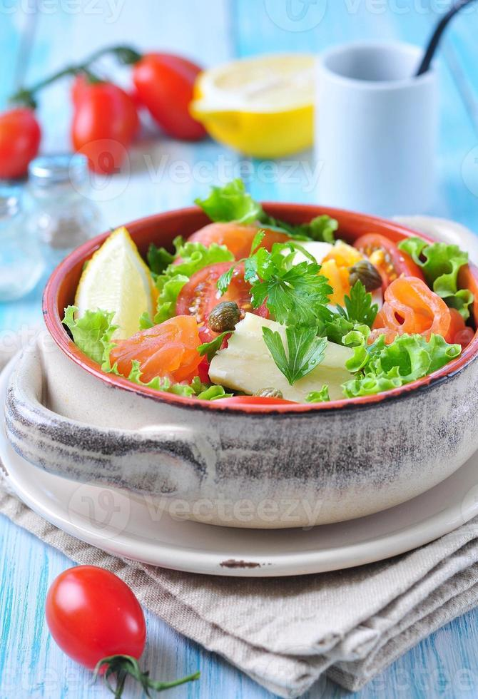 salad with salmon, lettuce, boiled eggs, cherry tomatoes, parmesan cheese photo