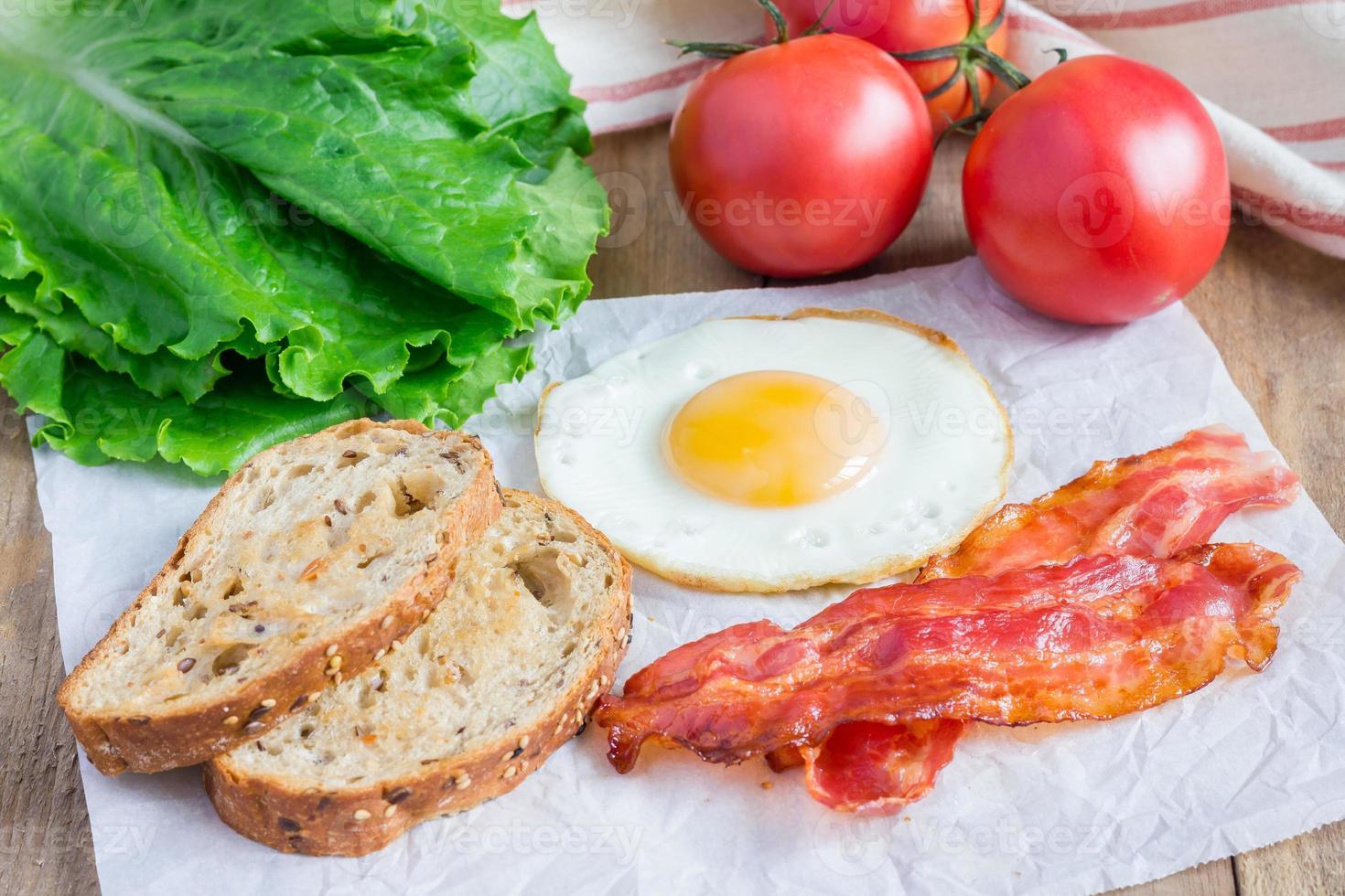 hacer bocadillo abierto con huevo, tocino, tomate y lechuga foto