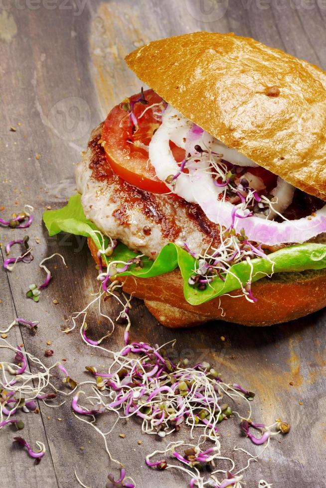 Primer plano de hamburguesa casera sobre fondo de madera foto