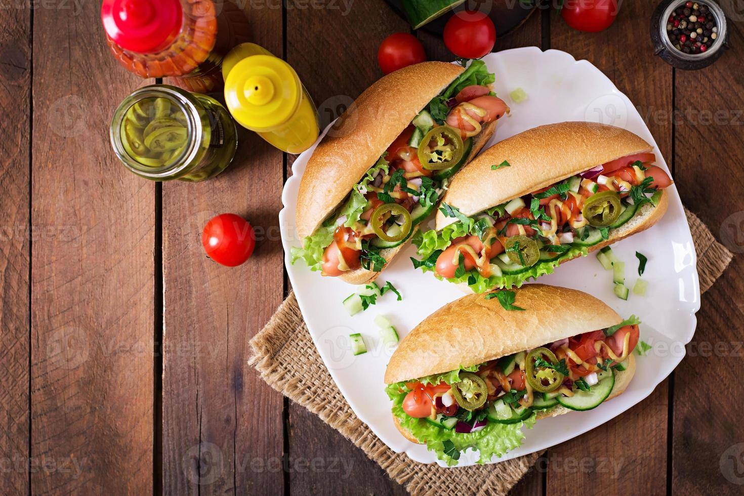 Hot dog with jalapeno peppers, tomato, cucumber and lettuce photo