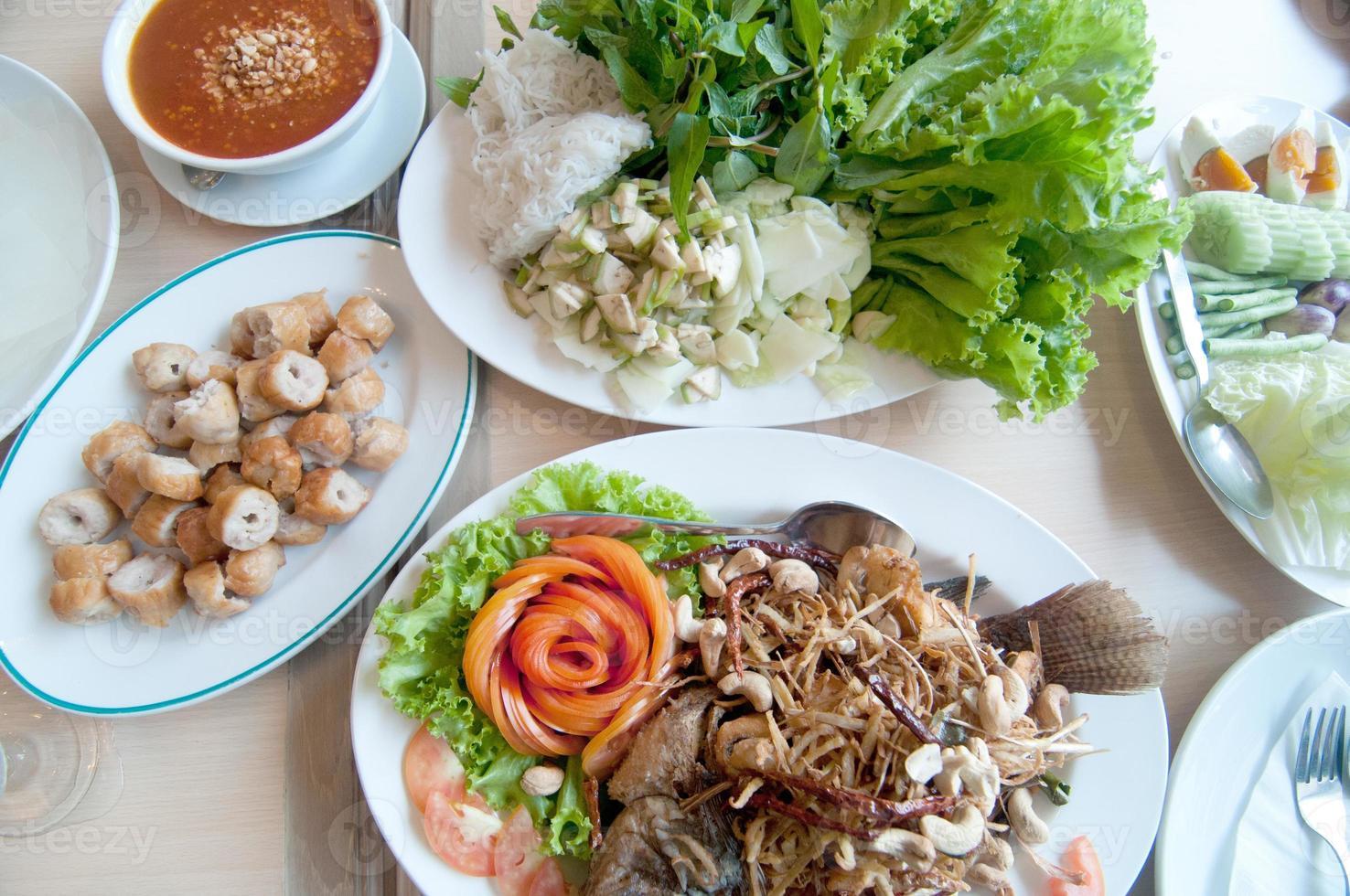 comida tailandesa en la mesa de comedor - pescado al horno, salsa de chile foto