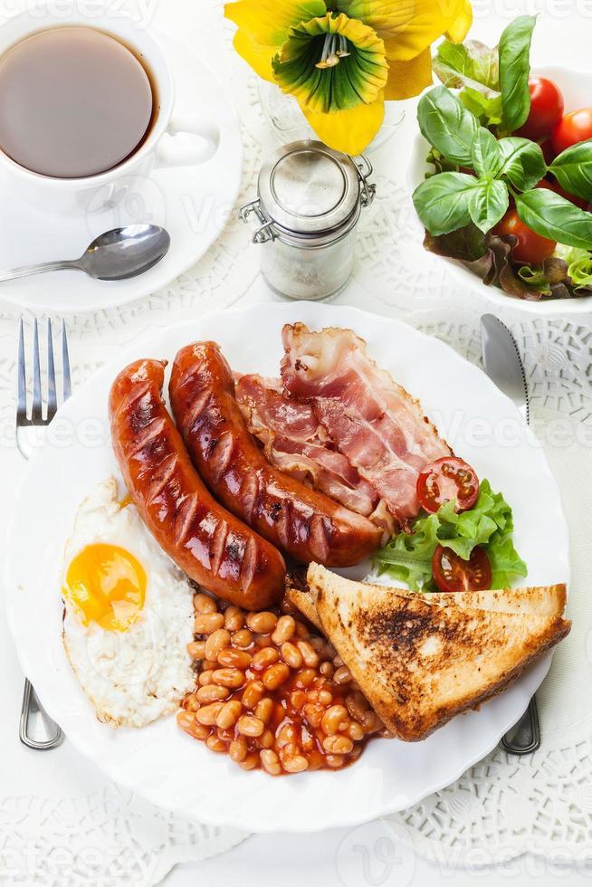 desayuno inglés completo con tocino, salchichas, huevo frito y al horno foto