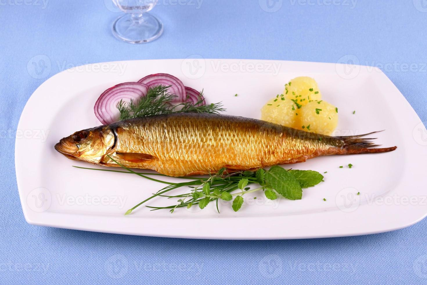 Kippers, smoked herring on a white plate with garnish photo