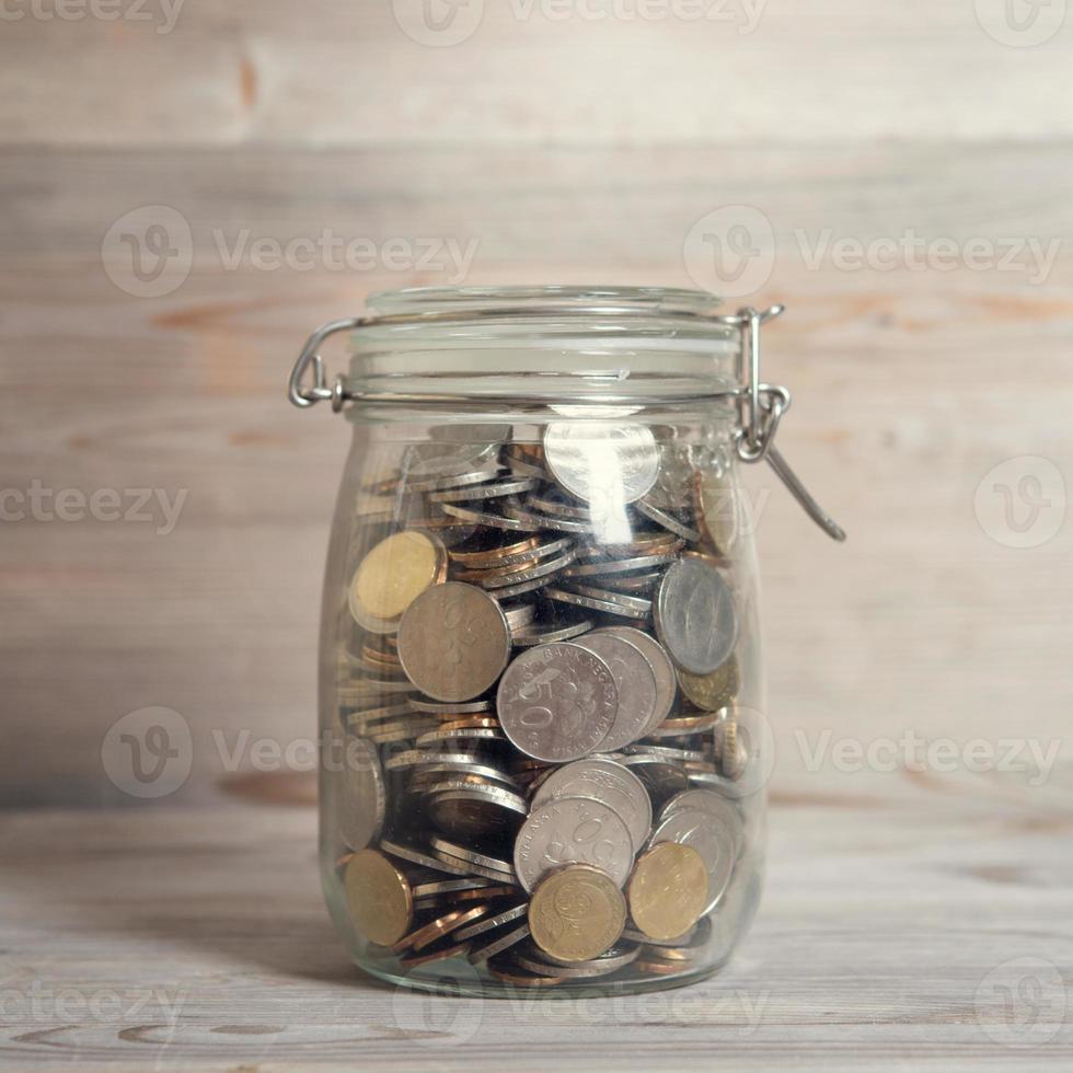 Coins in glass money jar photo