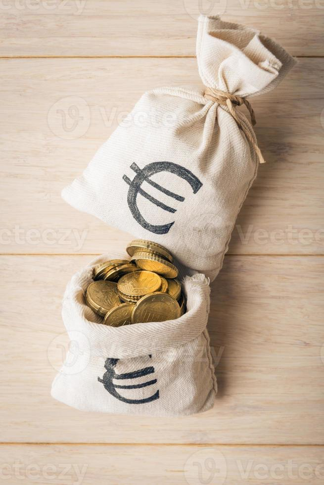 Money bags and euro coins on wooden background photo