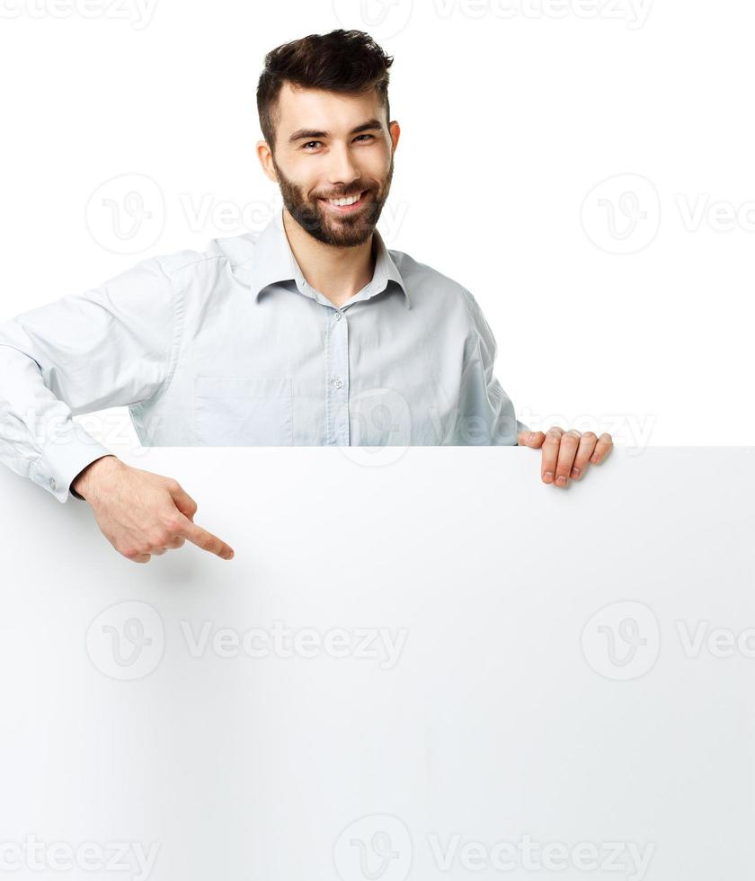 Young bearded man showing blank signboard, isolated over white photo