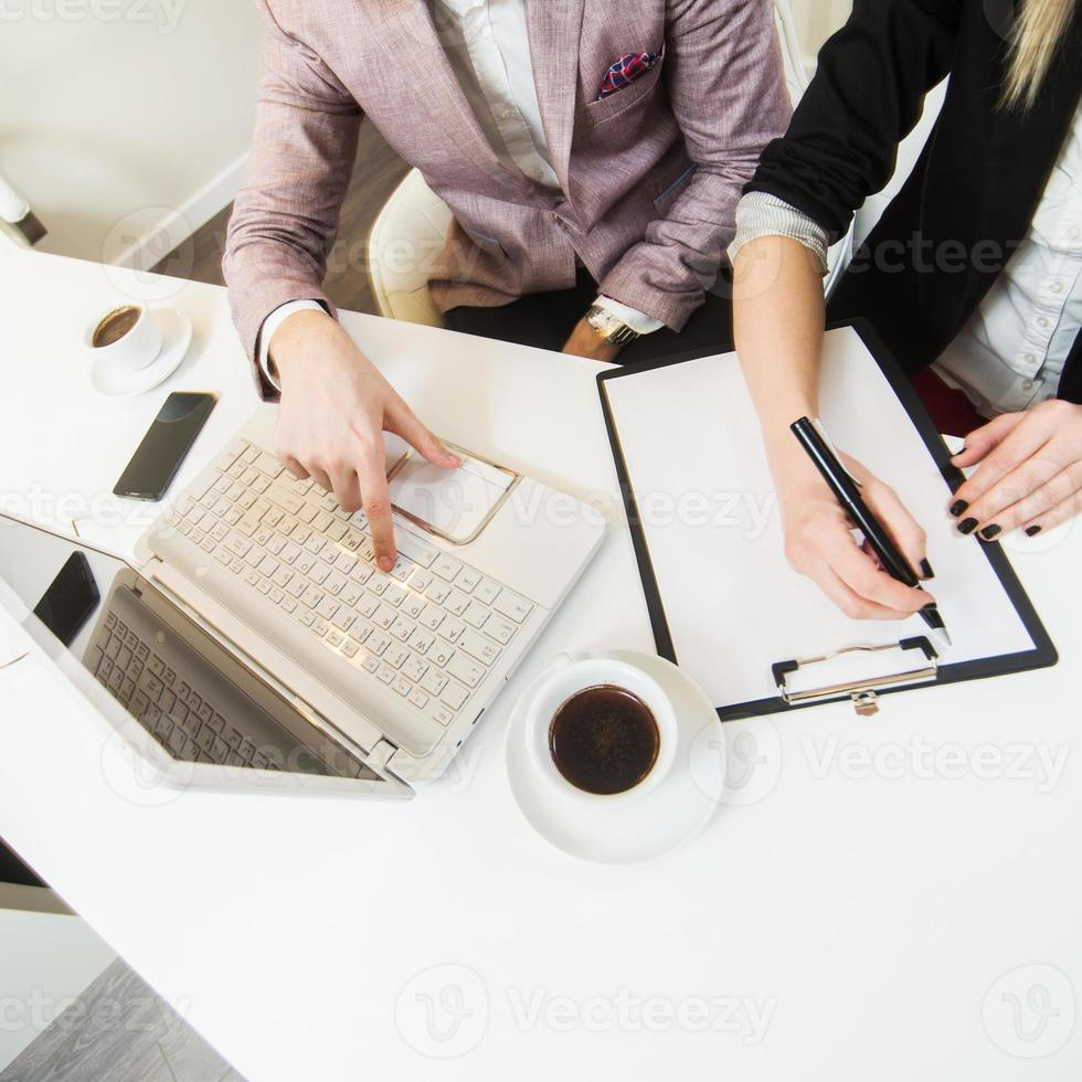 Overhead of two people working with laptop and clipboard photo