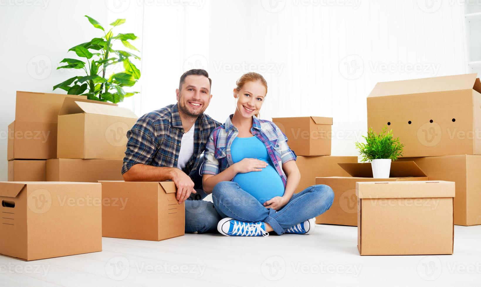 moving to  new apartment. family pregnant wife and husband with photo