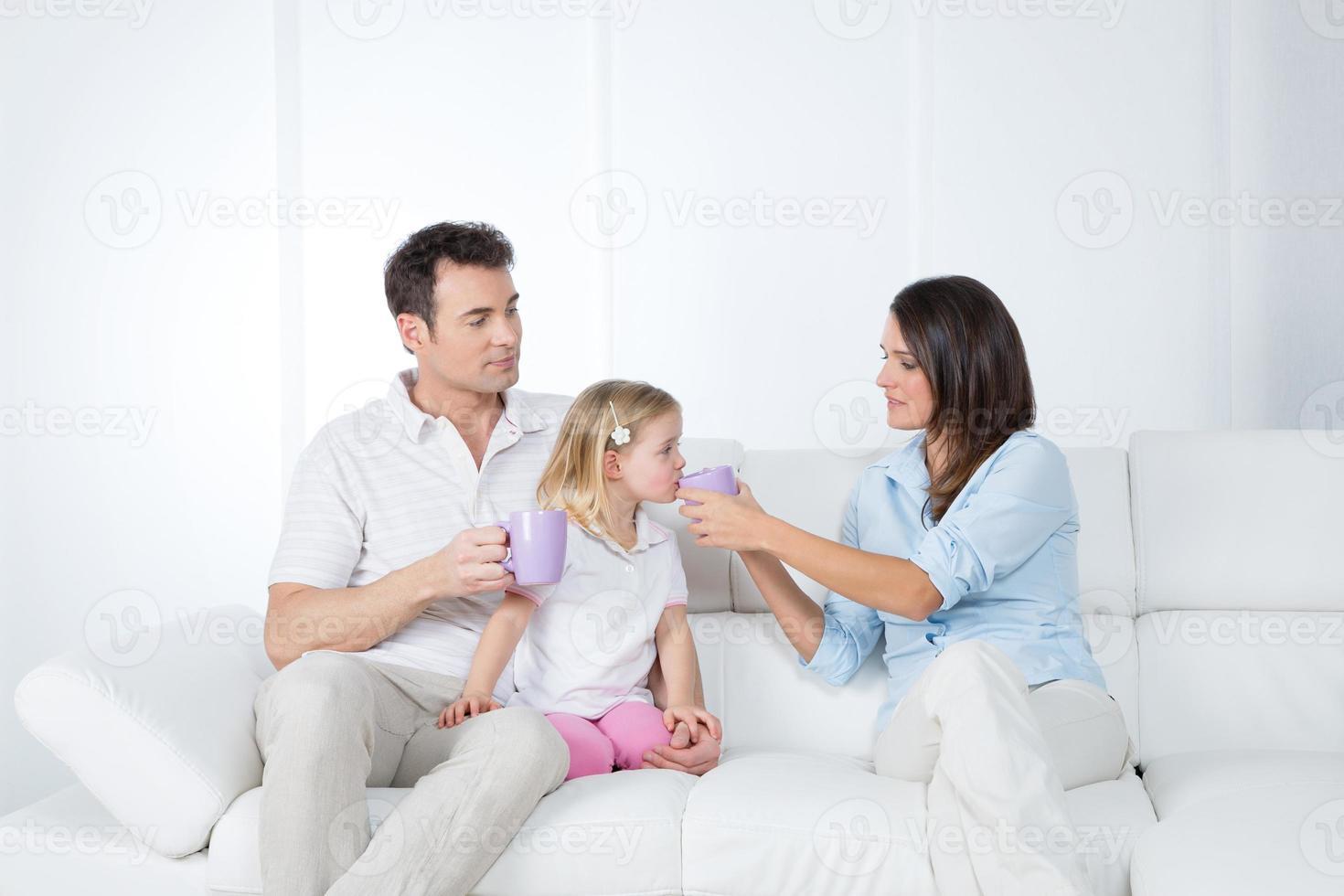 padres cuidadosos con hija pequeña foto