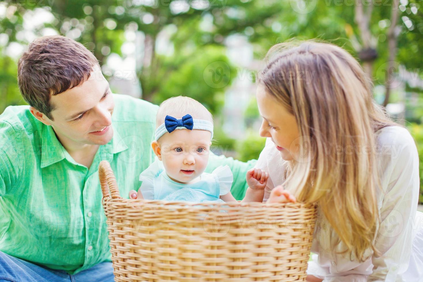 Happy couple with their baby in a laundry basket photo
