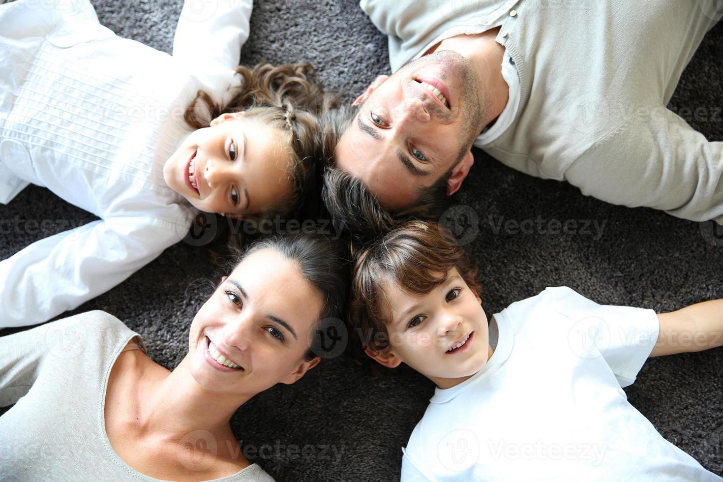 Happy family laying on floor, star shape photo