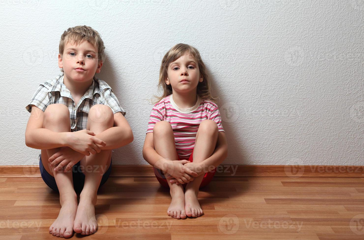 Thoughtful boy and girl sit leaning on the wall photo