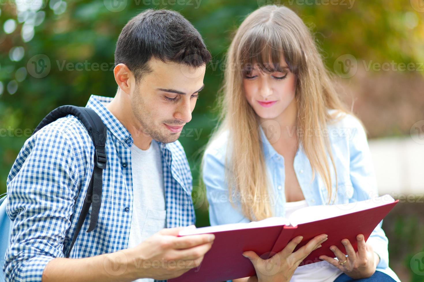 pareja de estudiantes leyendo un libro foto