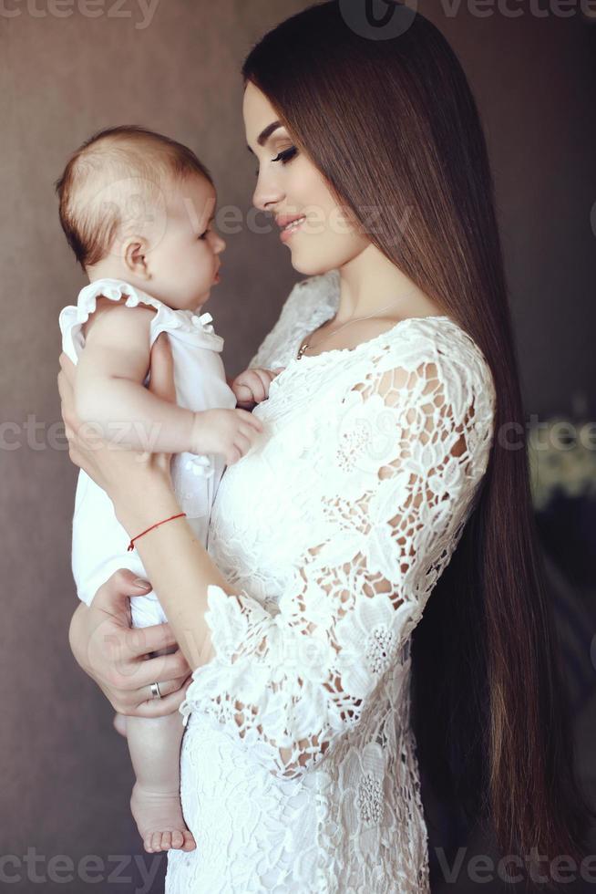 madre con cabello oscuro posando con su pequeño bebé adorable foto