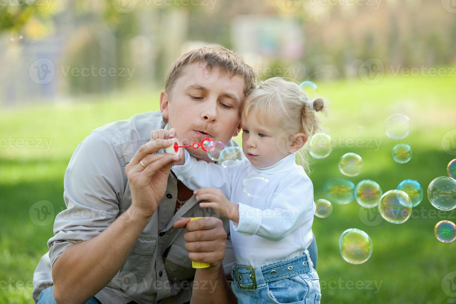 A dad and his daughter blowing bubbles in a park photo