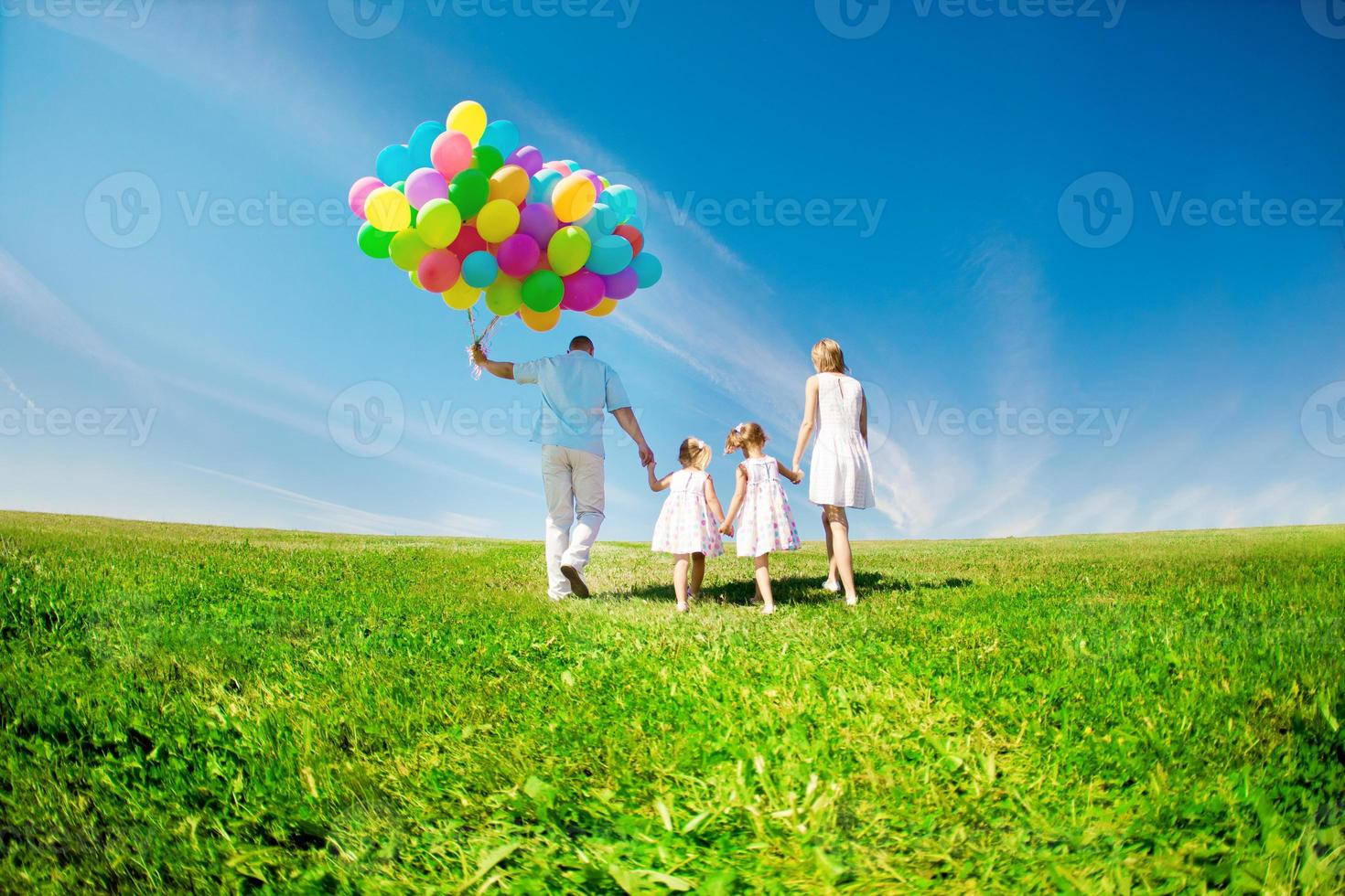 Happy family holding colorful balloons. Mom, ded and two daughte photo