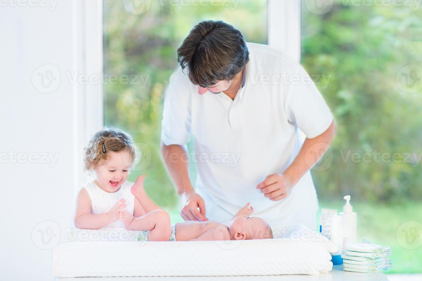 bebé recién nacido mirando a su padre y hermana cambiando pañales foto
