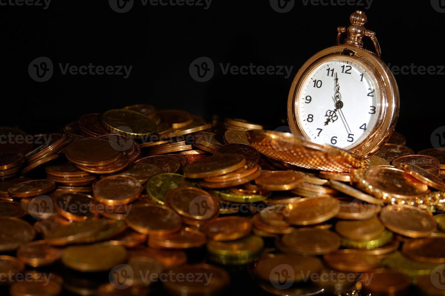 reloj de bolsillo y monedas foto
