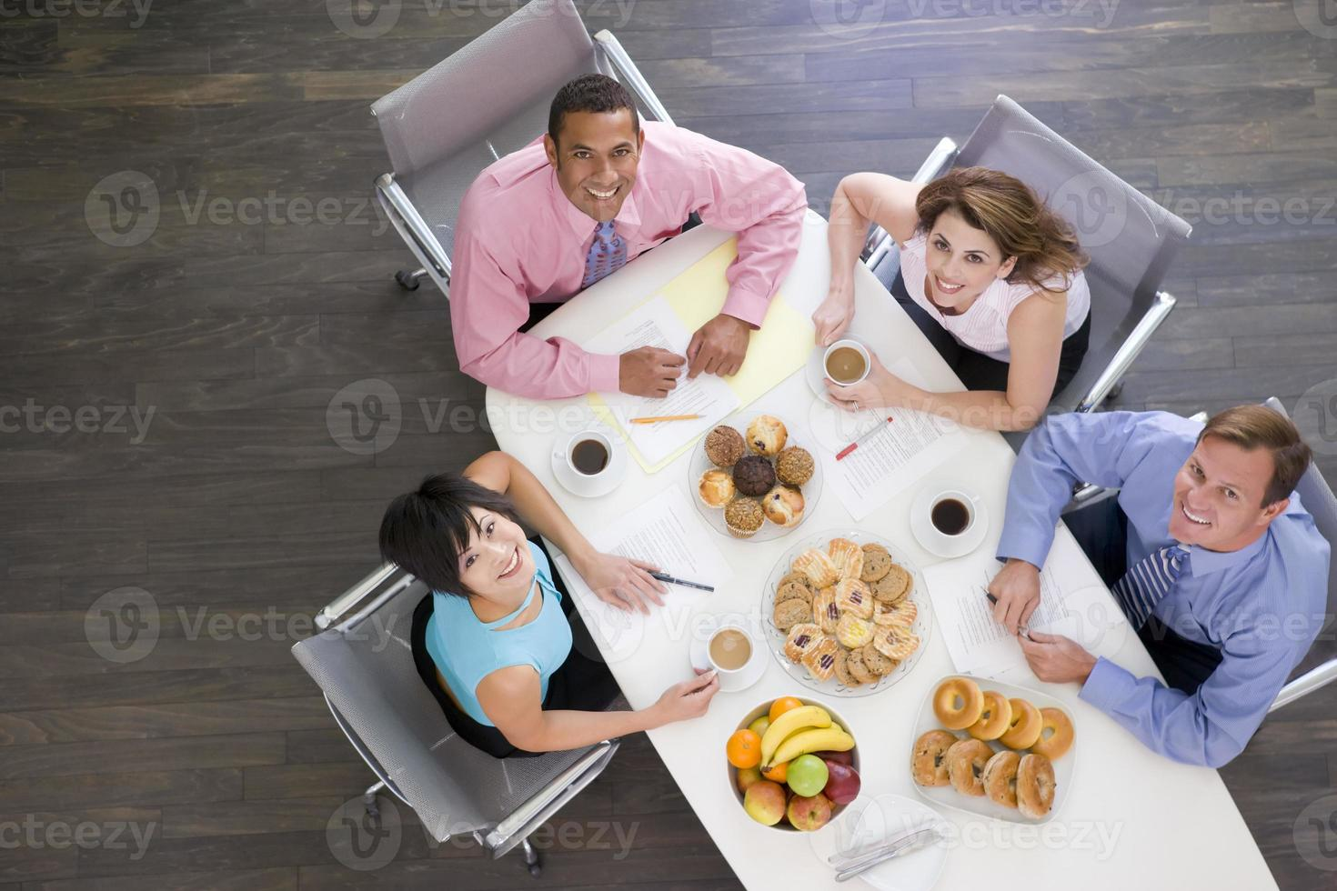 Four businesspeople at boardroom table photo
