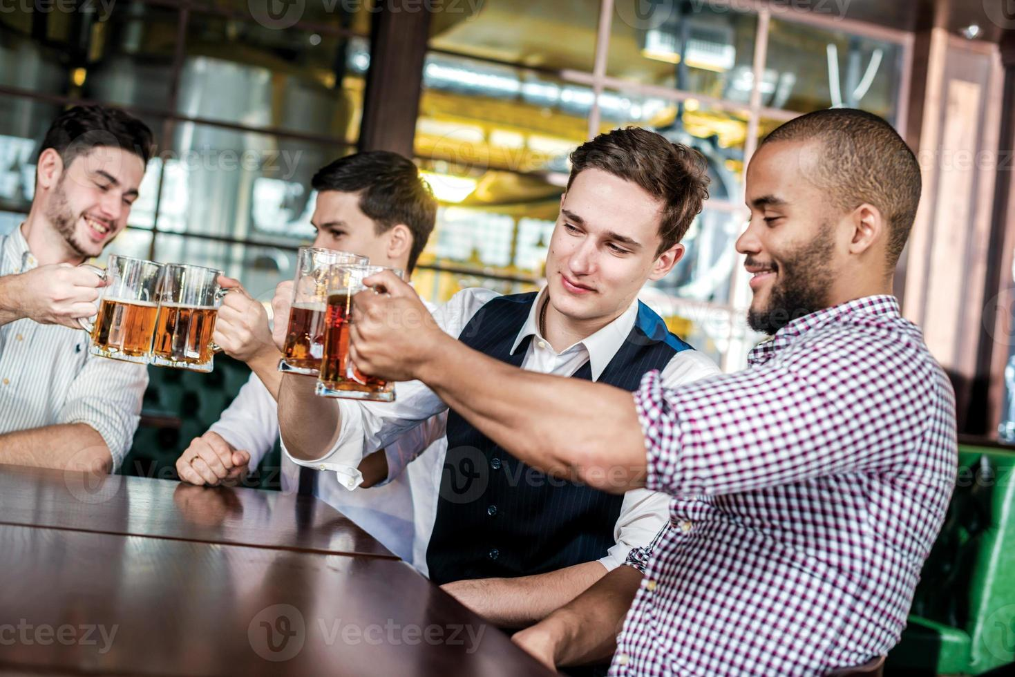 Four businessmen friends drink beer and spend time together photo