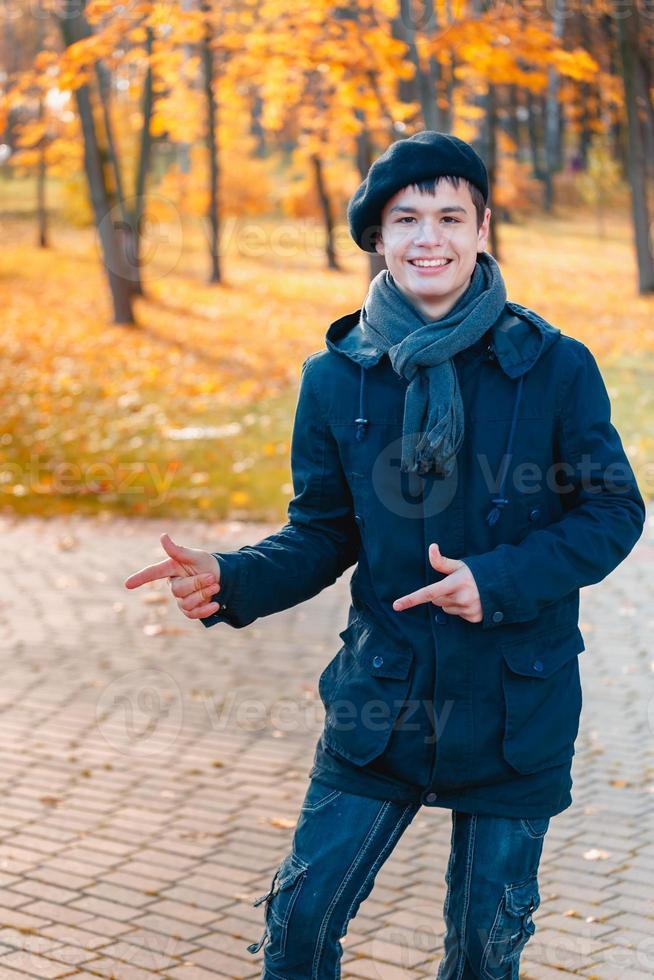 Happy teenage boy in the autumn sunny park photo