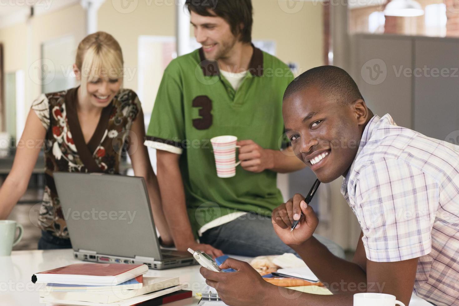 Hombre de negocios confidente con colegas usando laptop foto