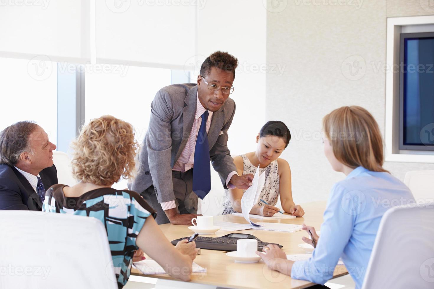cinco empresarios reunidos en la sala de juntas foto