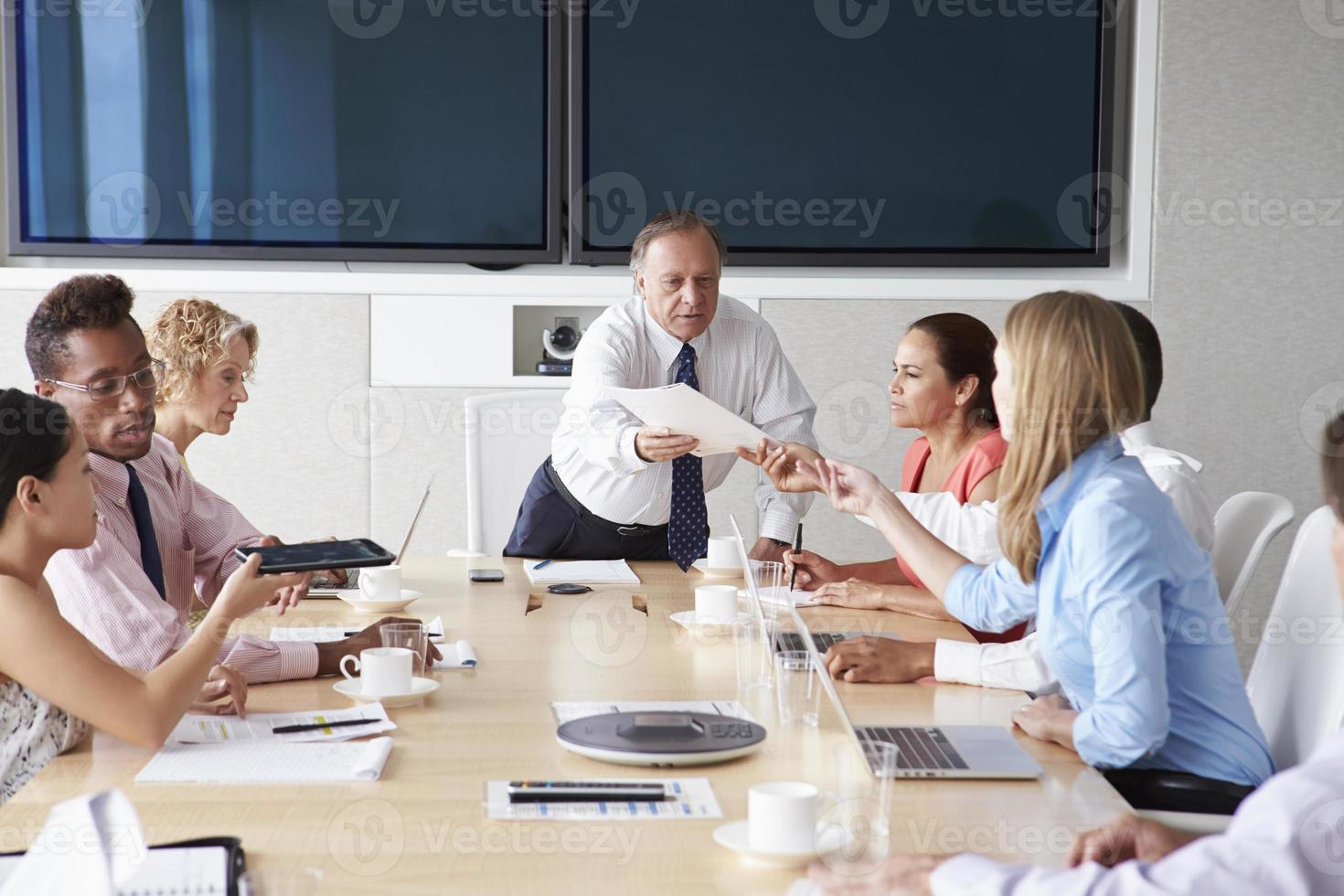 Group Of Businesspeople Meeting Around Boardroom Table photo