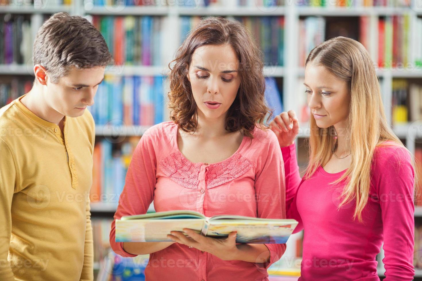 estudiantes y su maestra en la biblioteca. foto