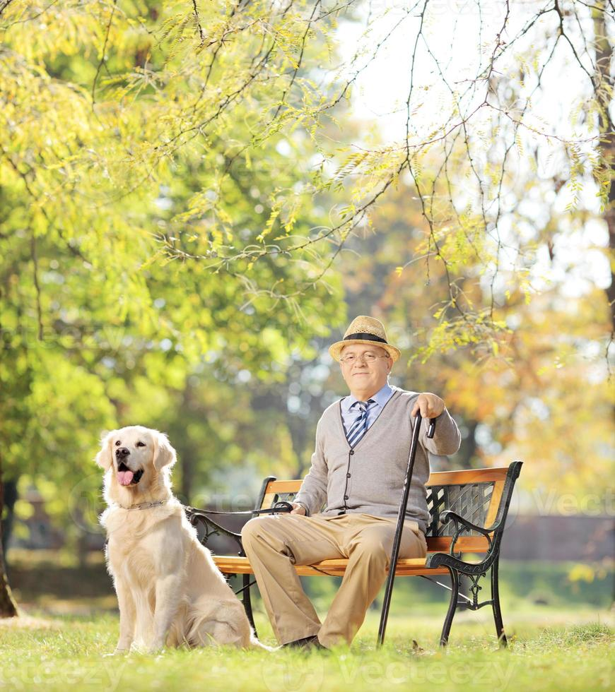 Senior man relaxing in a park with his dog photo