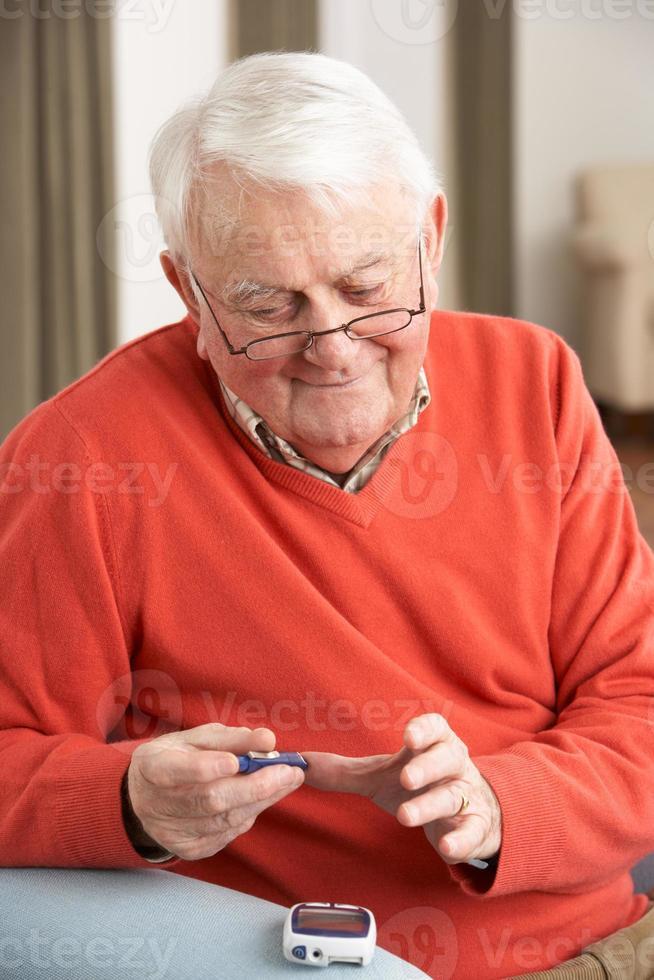 Senior hombre haciendo análisis de sangre de glucosa en su casa foto
