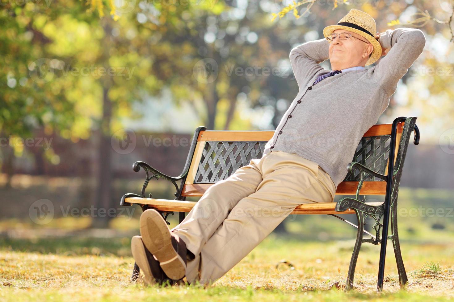 Pensionista relajado sentado en el banco en el parque foto
