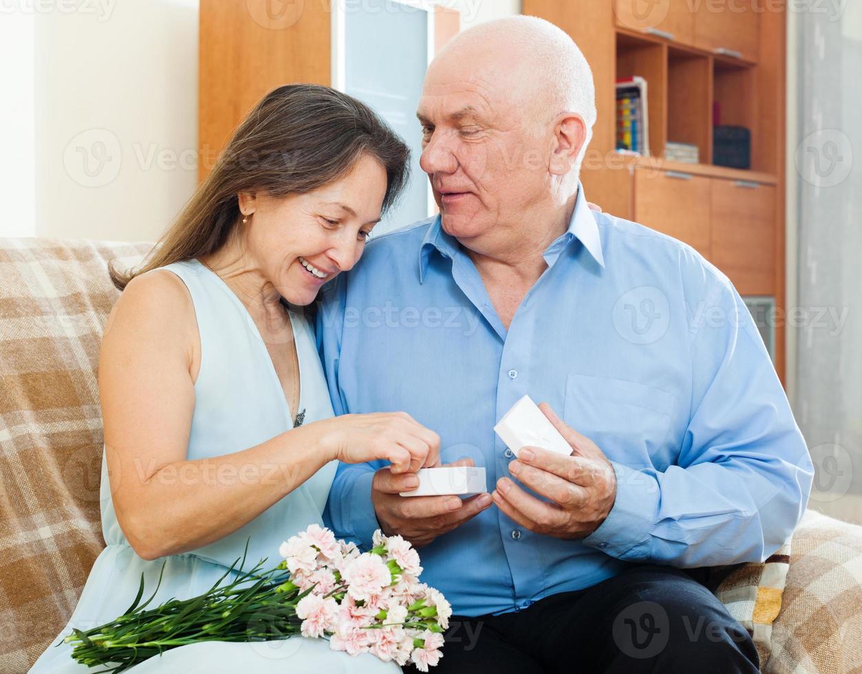 mujer madura feliz mirando joya foto