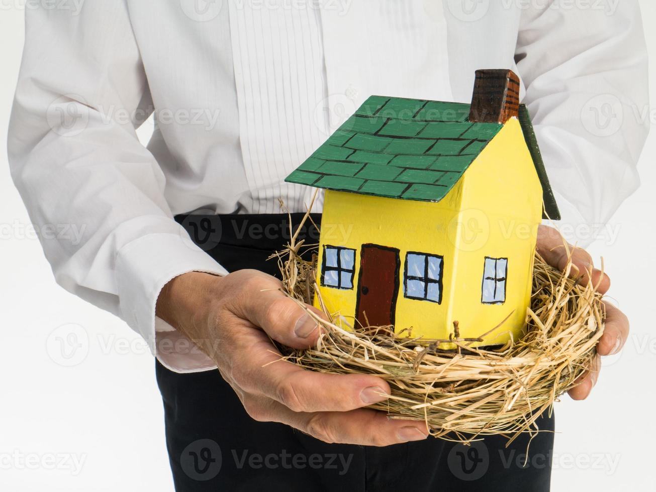 Man holds birds nest with miniature home inside photo