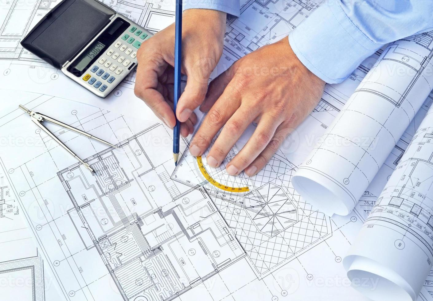 Hands with tool and project drawings photo