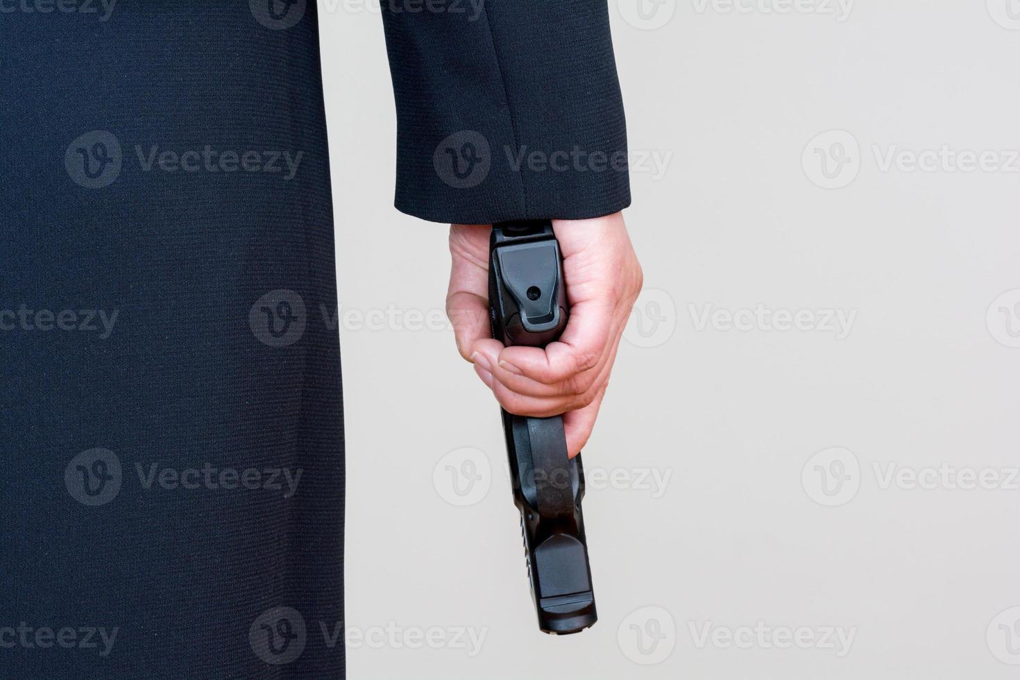 Woman holding hand gun on white background photo
