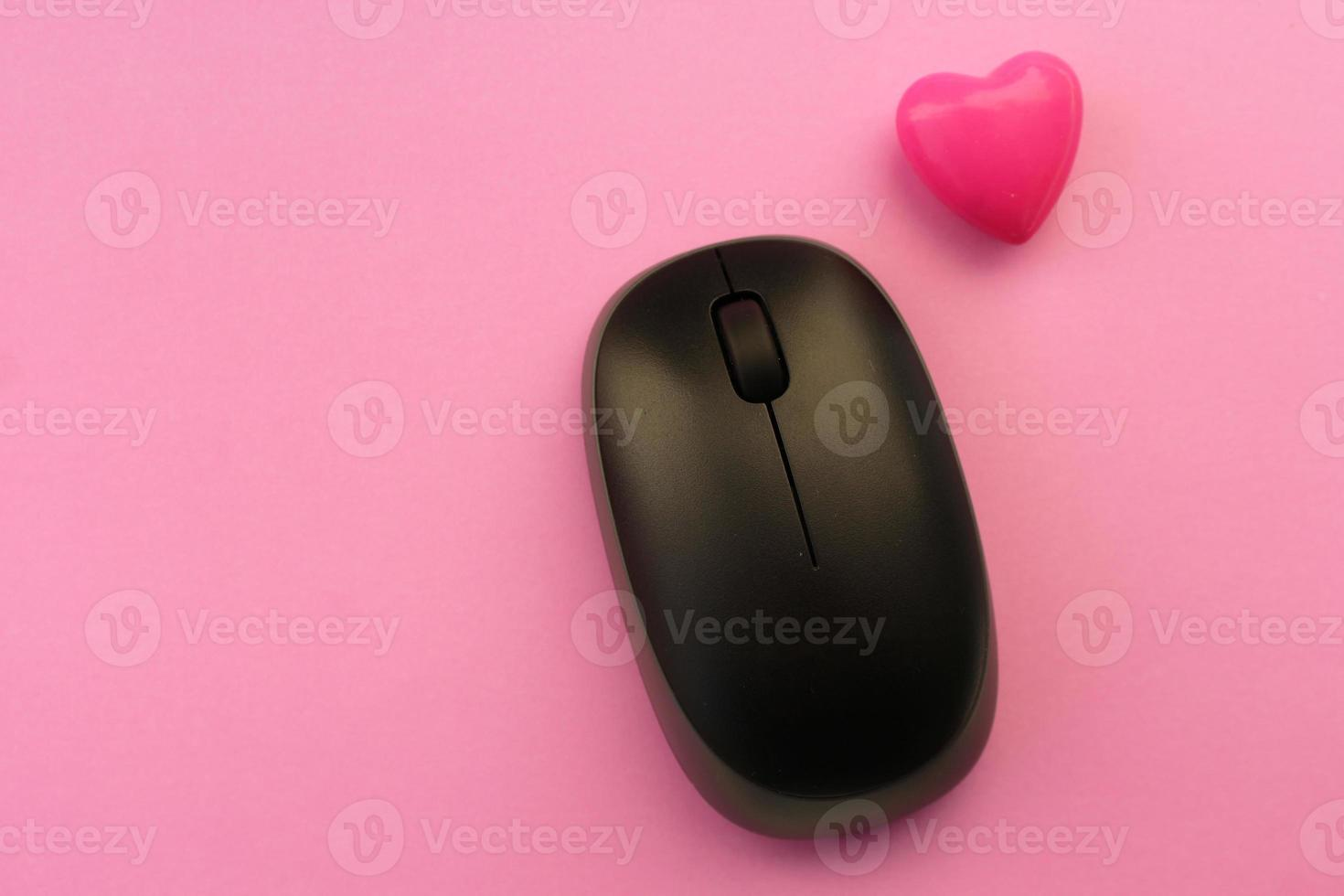Wireless computer mouse and pink heart - love technology concept photo