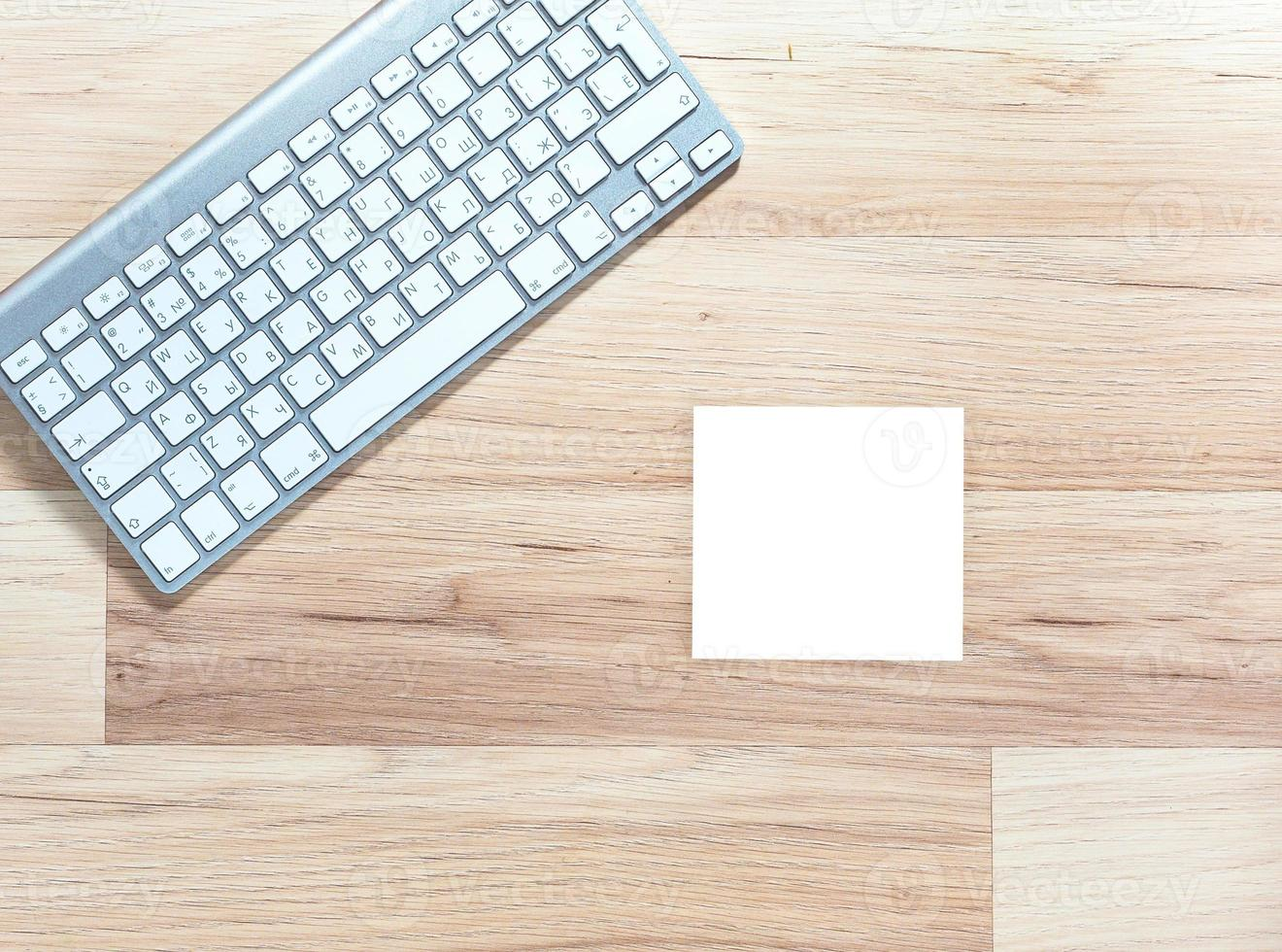 metal keyboard and blank white notepad on wooden table photo