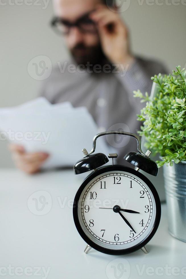Hombre con papeles sobre la mesa con reloj despertador portátil foto