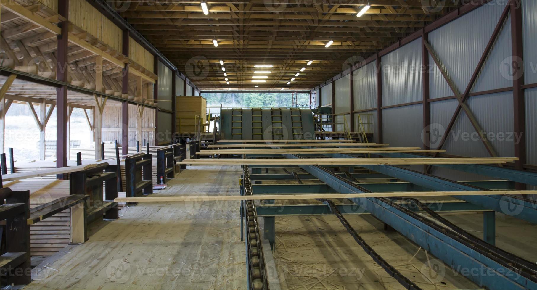 cortar tablones de madera en transportador en aserradero foto