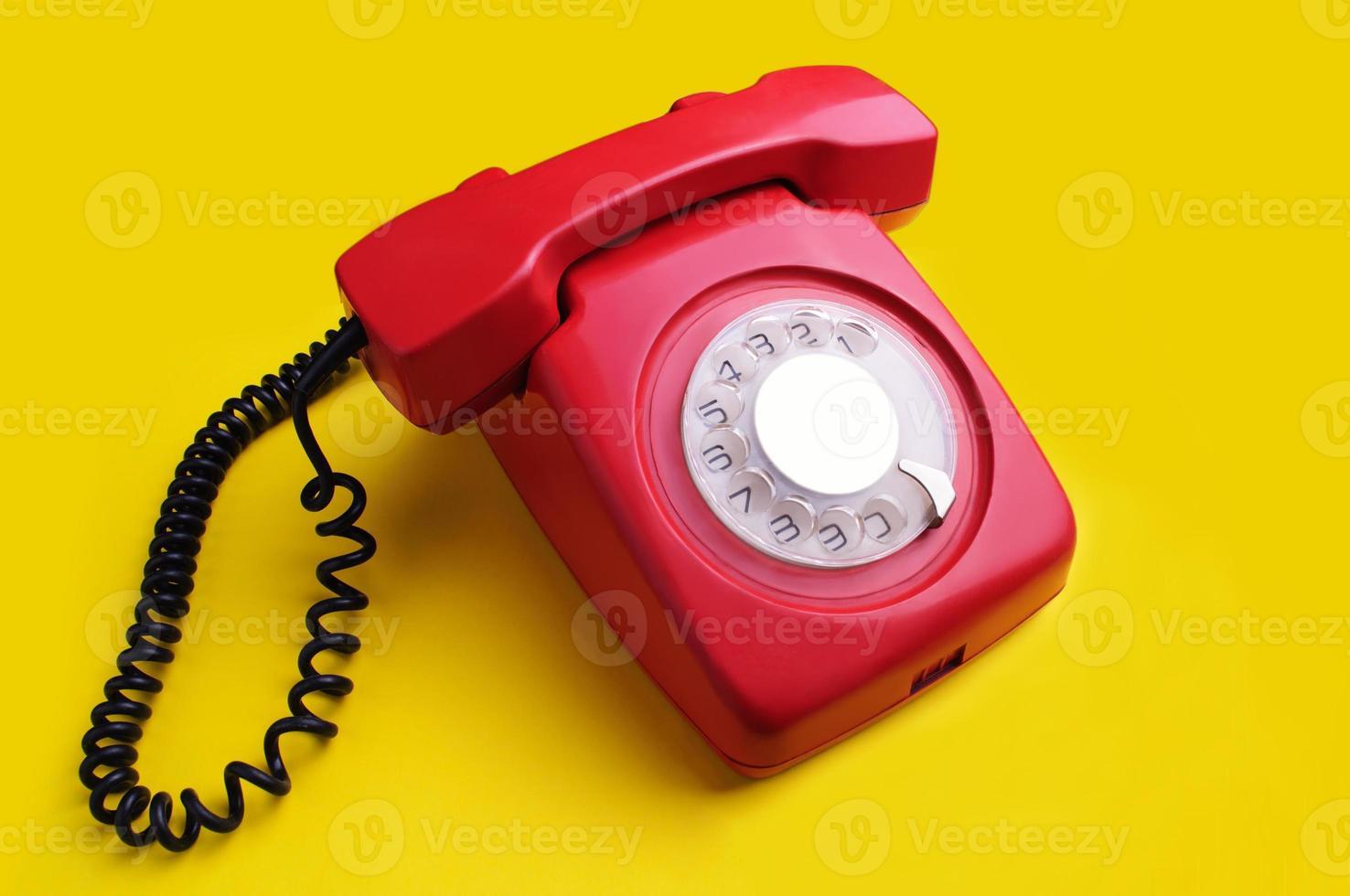 Red retro telephone on yellow background photo