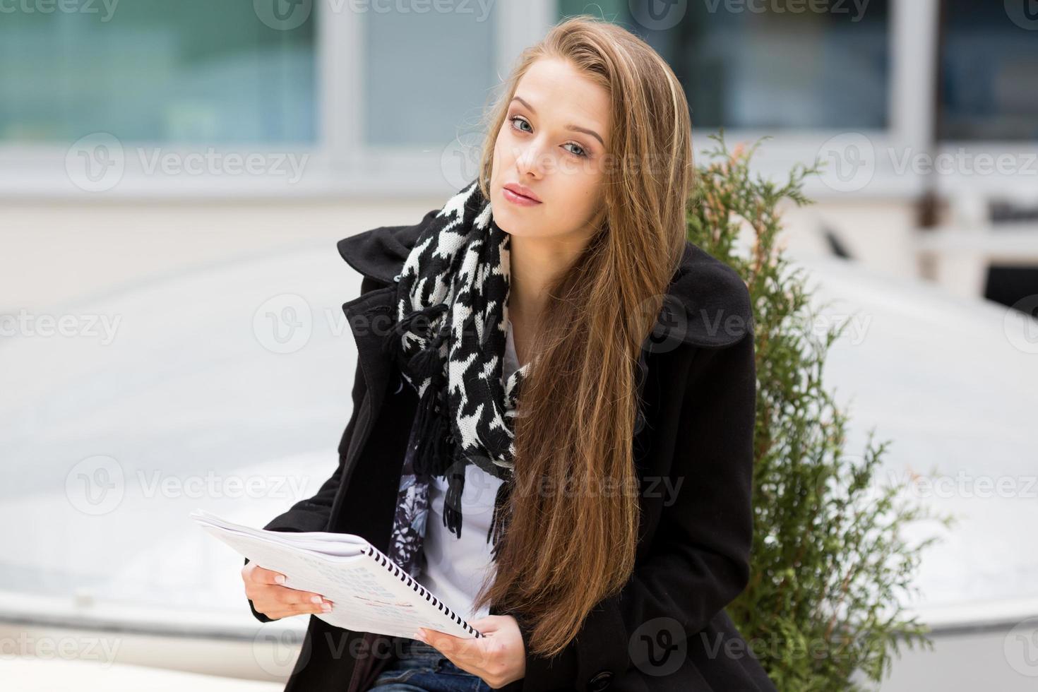 Joven mujer sentada con un libro. foto