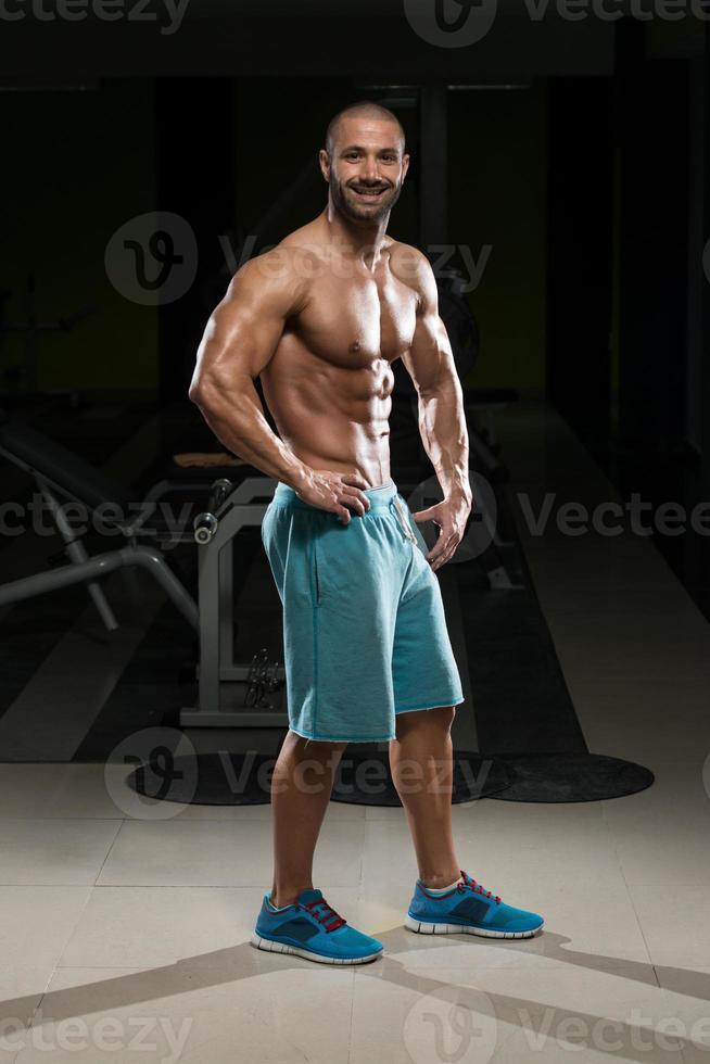 man in de sportschool met zijn goed getrainde lichaam foto
