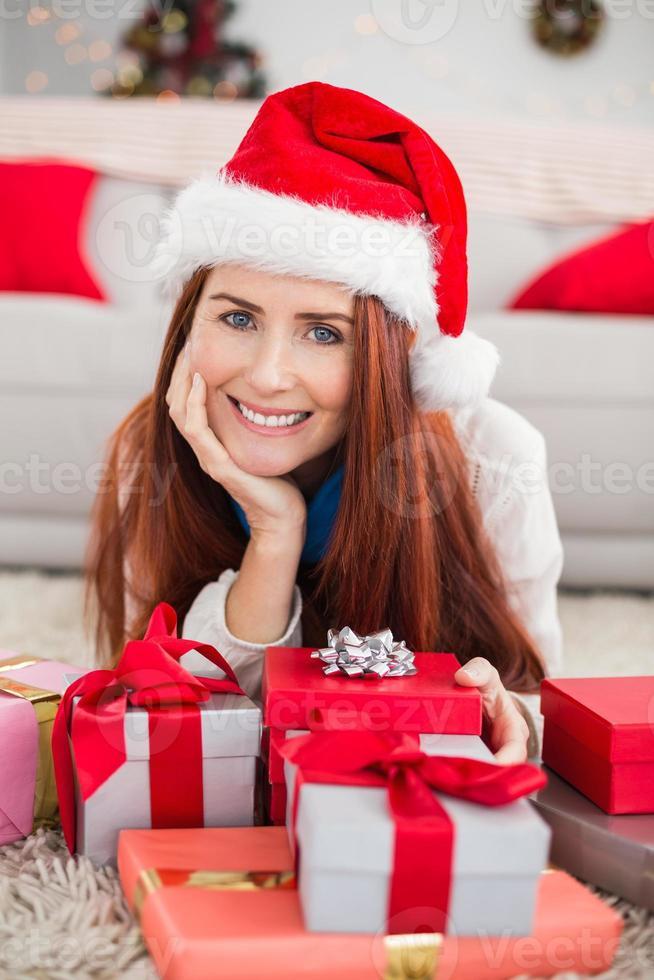 ruiva festiva, sorrindo para a câmera segurando o presente foto