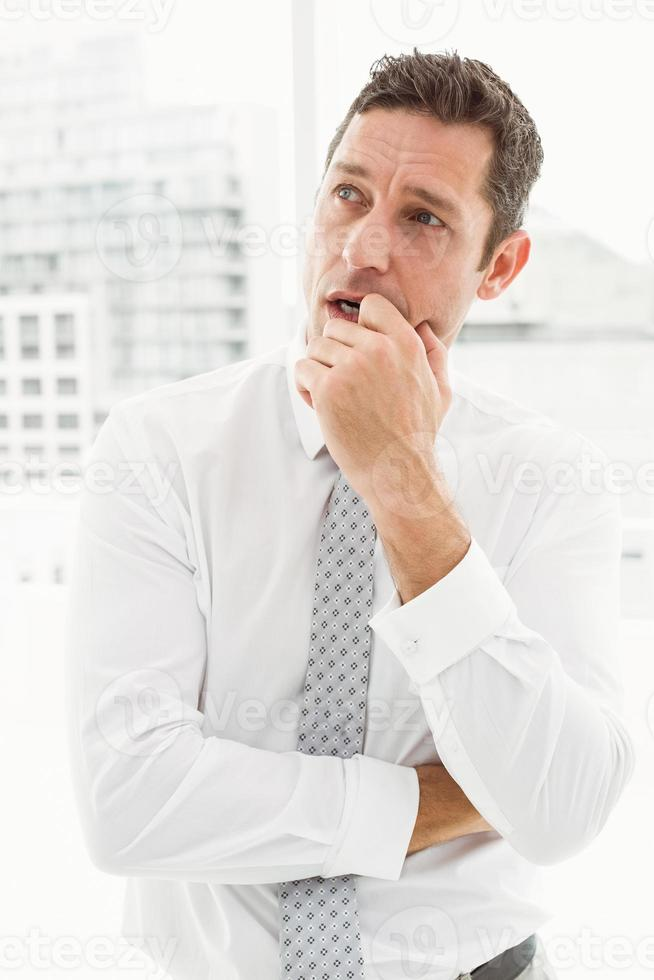 Thoughtful businessman looking away at office photo
