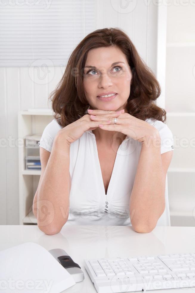 atractiva secretaria madura está reflexionando en la oficina. foto