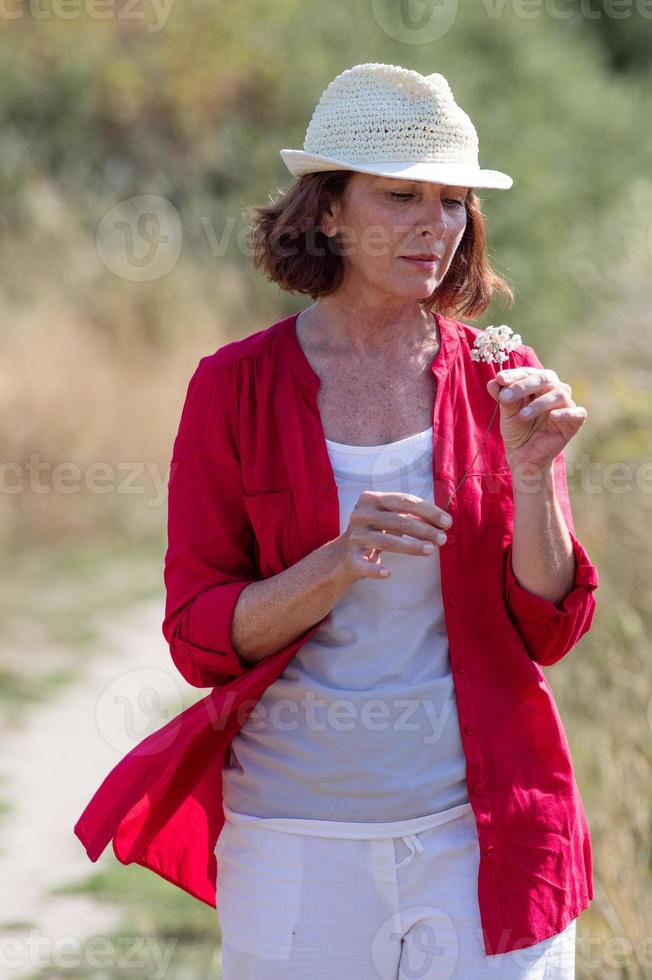 relaxed aging woman enjoying summer walking in the countryside photo