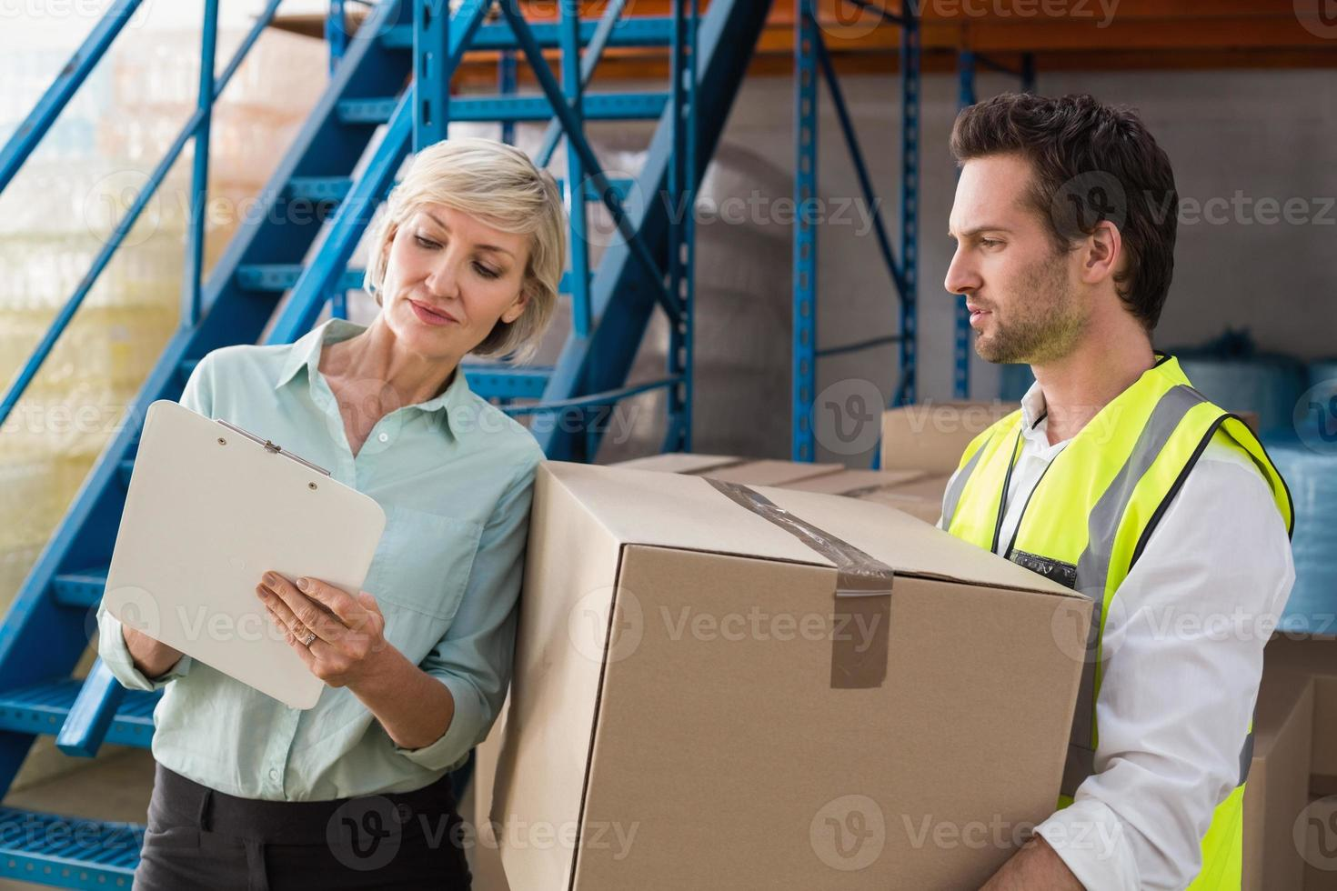 Warehouse manager and worker looking at clipboard photo