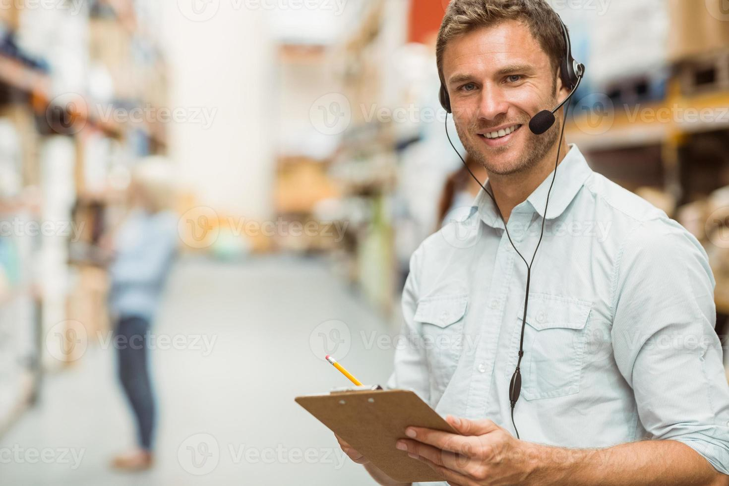 Warehouse manager wearing headset writing on clipboard photo